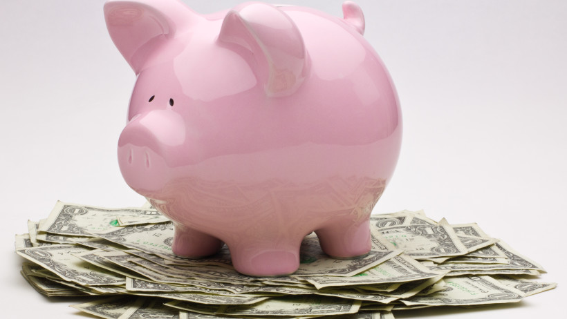 pink-piggy-bank-on-top-of-a-pile-of-one-dollar-bills
